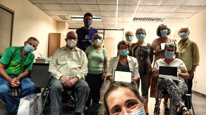 Grupo de usuarios del programa Cultiva Mente de AFAGA mostrando sus tabletas con los técnicos de AFAGA y Fundación Esplai también presentes.