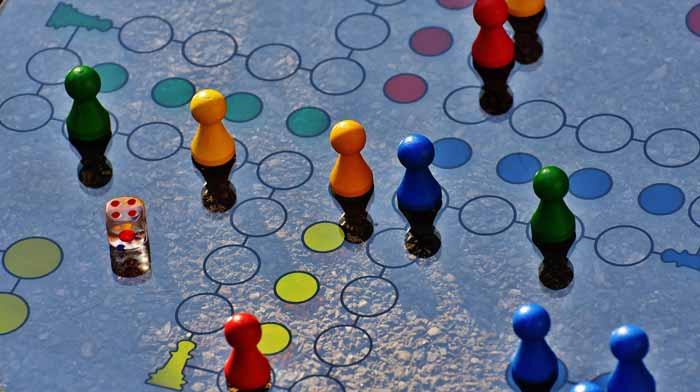 Tablero de juego tipo parchís con peones de colores varios