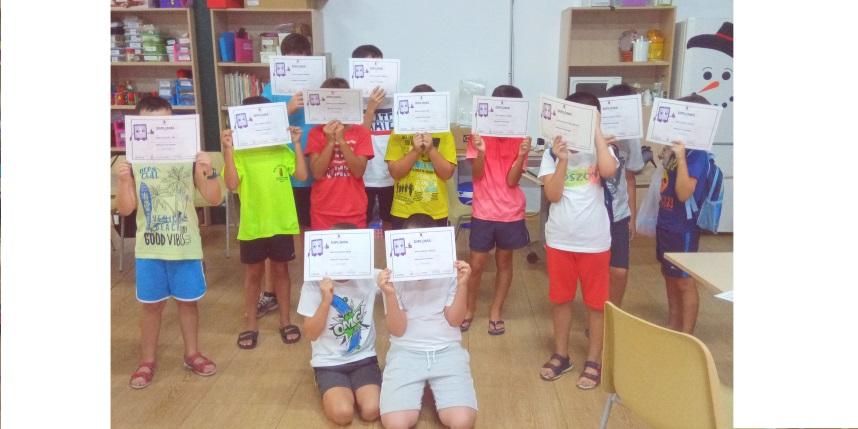 grupo de niños y niñas que se tapan la cara con el diploma de finalización del proyecto