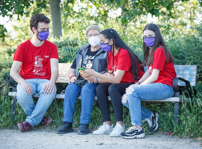 Jóvenes muestran móvil a mujer mayor